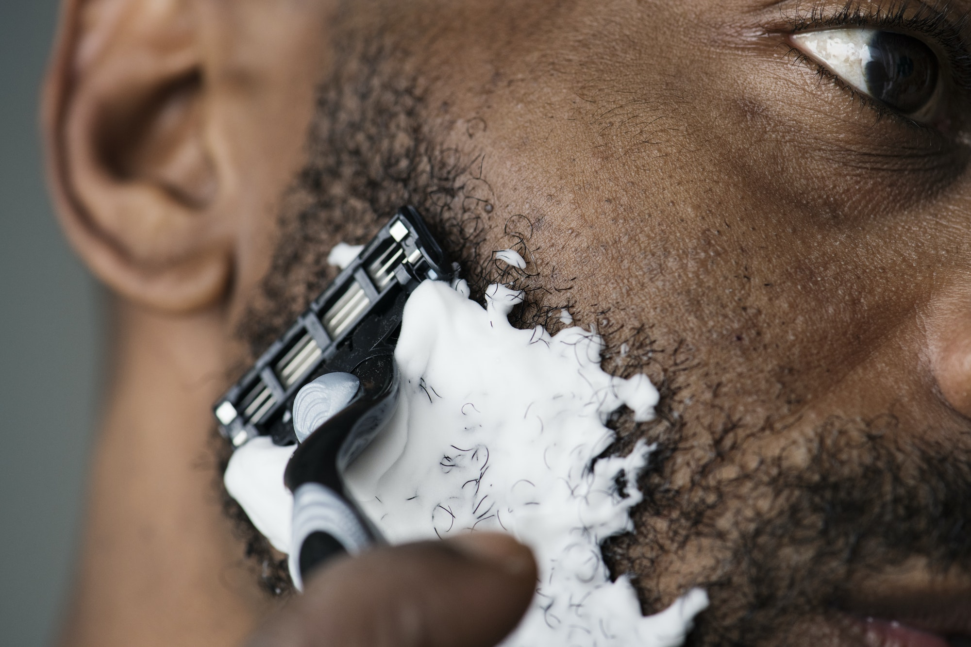 Black man shaving his beard