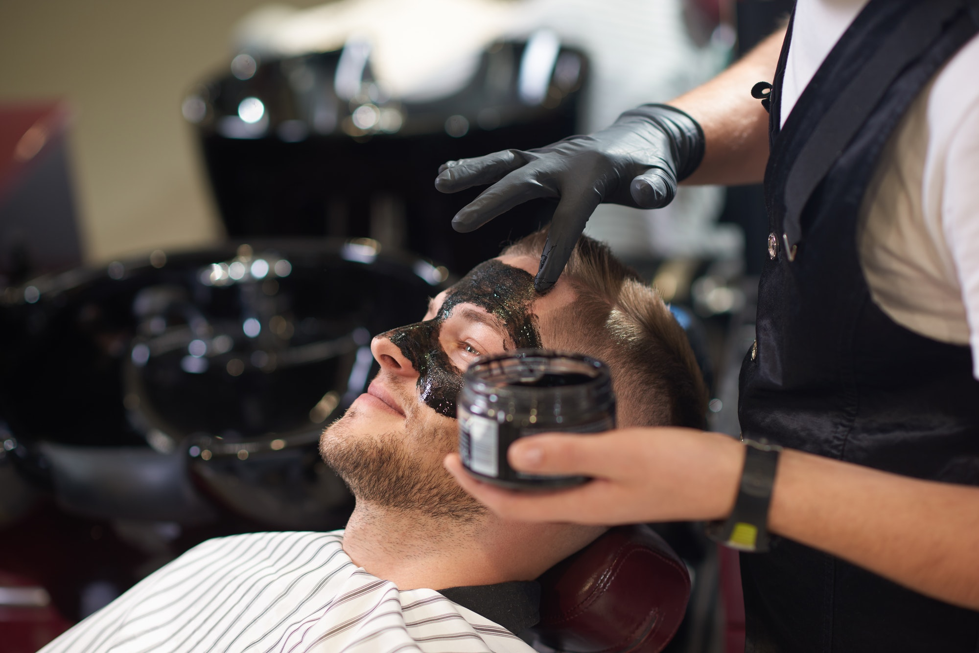 Side view of barber putting black mask on face of male